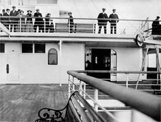 """Second class passengers are shown here gazing down at the photographer on """"A"""" deck. The aft end of the boat deck was available to second class as a promenade area. The morning air must have been chilly, most people are wearing warm coats."""