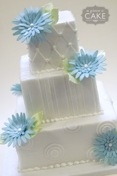 Wedding Cake  ... white on white panels ... pearls/dots between them ... layered flowers with lots of petals ... gerbera daisy look  simple and elegant with a touch of whimsy ...