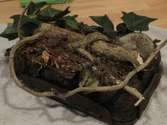 Find a small container and glue on some forest twigs and leaves.