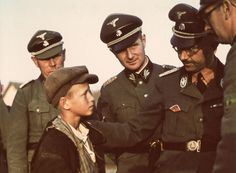 """Reichsführer-SS Heinrich Himmler talks through an interpreter to a local boy during an inspection tour of Belarus. The fatherly posture of the Nazi arch-killer is deceiving: Belorussians, like all Slavs, were to be exterminated through famine and """"special measures"""" to make room for German settlers. To Himmler's right is his chief adjutant Karl Wolf. 1942."""