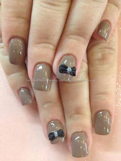Nude polish with black 3D bow over acrylic nails