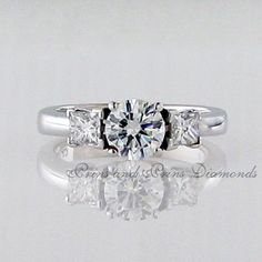 Centre diamond is a round brilliant cut diamond with 2 = princess cut diamonds set in white gold Thing 1, Three Stone Rings, Princess Cut Diamonds, Diamond Cuts, Centre, White Gold, Engagement Rings, Jewelry, Enagement Rings