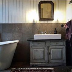 BADRUM ➰ Behagligt och charmigt badrum med pärlspont i grön umbra och kalkstensplattor som går från golv upp till halva väggen. Kommoden är ett gammalt skåp köpt på nätauktion och toppskivan är behandlad med kimrökssvart linoljefärg 2 ggr och bivax. Det är @13northernlights som visar upp badrummet hos sin mamma @karinsgarden Tack för att ni taggar #renoveringsdamm