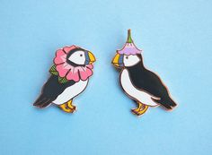We love puffins, and we love flowers! This pair of puffins look great together or separated! On the left is Hibiscus Neck Collar Puffin, and on the right is Morning Glory Puffin, with a little morning glory flower for a hat! Based on Natelles original illustrations. The pins are a limited edition of 250, are hard enamel with a copper metal finish, with a rubber clutch back. Hibiscus Puffin is 1.25 tall, while Morning Glory Puffin is 1.65 tall (that extra bit of stalk adds to the height!)…