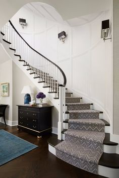 Paneled walls lend subtle distinction to the curved staircase anchoring this entry. - Elegant Homes ®/ Photo: Werner Straube / Design: Christine Hughes