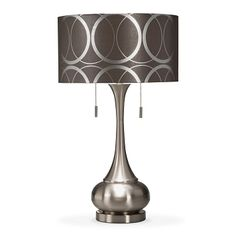 Right Round. Marvelously modern, the Kelly table lamp will shine a cool new light on your home d´cor. The dark gray shade features a bold, geometric silver ring design that coordinates perfectly with the brushed nickel finish on the base. Look no further than the Kelly lamp for the ultimate in hip, contemporary style.