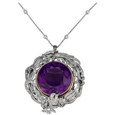 39.29 Carat Amethyst Diamond Platinum Pendant. A majestic 39.29-carat Siberian amethyst showcases its regal purple hue in this convertible Belle Époque pendant brooch. A wonderful foliate setting crafted of platinum and adorned with approximately 2.75 carats of shimmering white diamonds encircles the amethyst in this Edwardian-period piece.   Approximately .51 carats of white diamonds are mounted in the contemporary 18K gold chain. c 1910