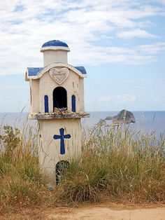 Wayside shrine between Arillas and Agios Stefanos, Greece. This probably marks a spot where someone died in a car accident. I saw many of these as I drove around the islands.
