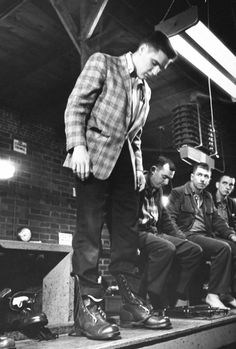 Singer/Army Pvt. Elvis Presley (L) clad in plaid sport coat & slacks as he stands, testing the fit of unlaced Army shoes he has just put on, while being issued his Army gear as 3 other inductees look on fr. bench at Ft. Chaffee.