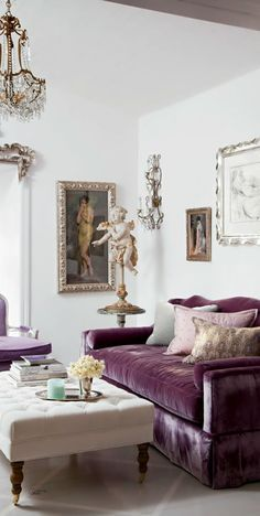 Glamorous living room with crystal and gold chandeliers, a tufted cocktail ottoman and plum-colored velvet sofa.