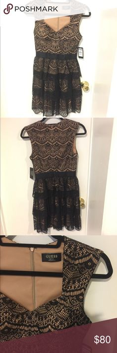 Guess Macayla Queen Anne Tiered Lace Dress Dress features full lining, nude with black lace, Queen Anne neckline, tiered skirt, padded bust, elastic waistline, A-line silhouette, and concealed back zipper closure. Guess Dresses
