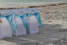 Suncoast Weddings style at a Florida beach wedding - crisp white chair covers with malibu blue sashes