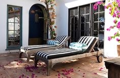 """The chaises are placed by the front door by design. """"That's where the beautiful vistas are,"""" says Heidi. """"We can spend an entire Saturday lying on them."""" Heidi ordered the cushion fabric online and accessorized the chairs with pillows from her own collection."""