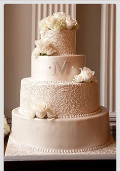 Clusters of coral and white flowers on cake with initial