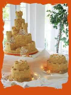 Sand Castle Wedding Cake - Done for a bride and groom who married in the Caribbean and had a hometown reception. Sand castle cake with 2 satellite cakes. Ground up cookie wafers make up the edible sand that covers the cake. The shells are made of gum paste used with a silicone mold and each indiviually highlighted with the brides color of  tangerine. The coral is piped from royal icing.