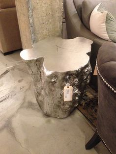 Silvered resin tree stump side table, next to bed