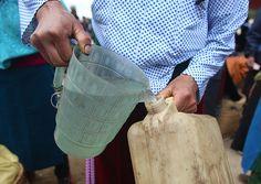 Rượu bán trực tiếp tại chợ được đong bằng chiếc ca, sau đó sẽ dồn vào can lớn nhỏ.