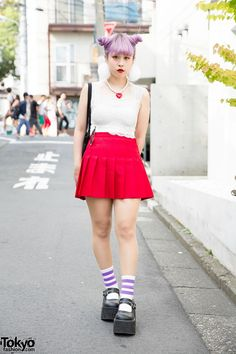 Serina is an 18-year-old fashion school student.  She has lilac hair in twin buns and red lipstick. Serina's outfit consists of a lace crop top and a red mini skirt, a black tote bag and platforms with sports socks. She accessorized with a pearls and heart necklace, a pompom earring and a studded cuff bracelet.
