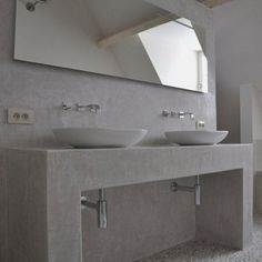 Modern concrete bathroom with double vessel sinks and wall mounted faucets.