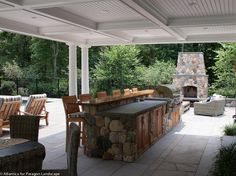 Outdoor entertaining with kitchen, bar, living area with fireplace, and dining room...