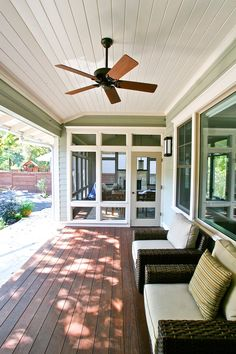Dark hardwood flooring extends out from the sunroom to this covered porch. A pair of brown wicker armchairs offers comfy seating, and a ceiling fan keeps the space cool during the hotter months.