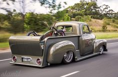 Advanced Designed Chevy pickup truck with a super custom bed riding low and loaded with a custom bike.