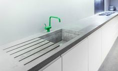 A custom concrete countertop fabricated by Lowinfo for a London architect is animated by a lime green Vola faucet.