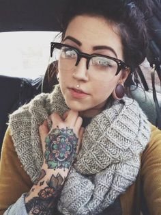 tattoo bulky scarf cool glasses pretty piercing and great hair  all combined to provide a beautiful example of how to do things right