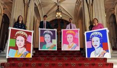 Exhibition curator Lauren Porter (left), Allan Chinn, Martin Clayton (second right) and Kate Stone (right) pose with Andy Warhol's Reigning Queens: Queen Elizabeth II portraits on the staircase leading to the Viewings Gallery at Windsor Castle, after being acquired by the Royal Collection in 2012