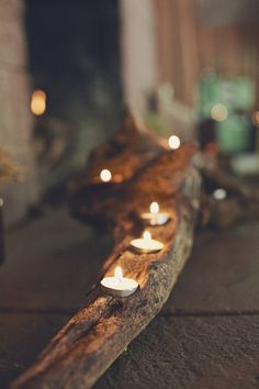Candles inset in wood branch.  Excellent for outdoor entertaining..