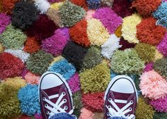 DIY Pompom Rug.  Oddly, I know how to make pom poms.  I also believe that if you use the right yarn and reinforce with textile glue....this *could be* hand washable.