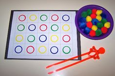 Pompom Tong Transfer, use the tongs (chopsticks) to place each pompom into a circle that is the same color as the pompom.