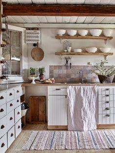 En köpmansdisk med marmorskiva från loppis blev bra förvaring i köket. På rustika hyllor visar Lindha upp antikt favoritporslin.