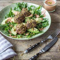 Die würzigen Hackfleischbällchen mit Pistazien erhalten durch den cremigen Rucola-Avocado-Salat einen frischen Begleiter.