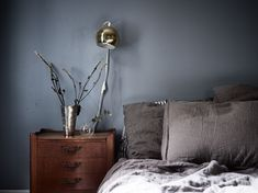 I like this bedroom with walls painted in a mixture of blue and grey. The velvet blue curtains and the brass wall lights make this look chique, while as the antique wooden side tables add character to the space. via … Continue reading → Blue Green Bedrooms, Blue Bedroom Walls, Bedroom Wall Colors, Bedroom Green, Blue Rooms, Home Decor Bedroom, Blue Side Table, Wooden Side Table, Side Tables