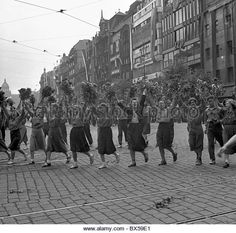 Prague - Czechoslovakia 1950.  Enthousiastic and cheering members of Czechoslovak Youth Union carry red flowers to honor the - Stock Image