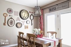 A breakfast room is brightened with vintage clocks, keys and an oversized invitation to EAT. Via Bless'er House