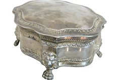 Vintage lidded silverplate box on paw feet with a blue velvet interior.