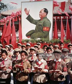 1968: A group of Chinese children in uniform in front of a picture of Chairman Mao Zedong (1893 - 1976) holding Mao's 'Little Red Book' during China's Cultural Revolution.