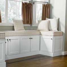 A good way to make some pretty storage -- A suite of 18-inch-deep by 24-inch-high cabinets typically used above refrigerators are set atop a platform on the floor, offering a sweet spot from which to cheer on the cook.  Shown: Stock Annapolis door in white thermofoil over MDF, about $125 per linear foot; available from American Woodmark  so doing this under front windows