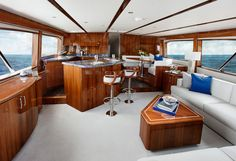 Hatteras GT A wide-angle lens view of the salon and galley: All wood is high-gloss, counters are granite. Notice the custom coffee table and the matching woodwork to the twin pedestal stools. Note the longitudinal varnished battens in the overhead. Boat Interior, Interior And Exterior, Interior Design, Yacht Design, Boat Design, Hatteras Yachts, Small Yachts, Living On A Boat, Sport Fishing