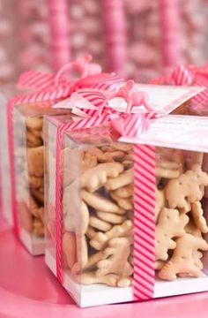 A clear box filled with animal crackers trimmed in pink is a sweet 1st birthday party favor.  See more first girl birthday party ideas at www.one-stop-party-ideas.com