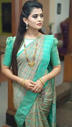 In a green color checks saree and puff high neck elbow length sleeve blouse design Pattu Saree Blouse Designs, Simple Blouse Designs, Stylish Blouse Design, Fancy Blouse Designs, Bridal Blouse Designs, Sleeves Designs For Dresses, Sleeve Designs, Designer Saree Blouses, Blouse Models