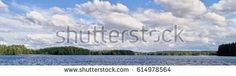 Stock Photo: Panorama lakeside landscape with dramatic cumulus clouds in the bright summer day scene in Finland. -