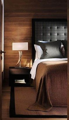 Wood paneled walls, the simple bedding, the grey flannel headboard & the simple sisal rug, bordered in black