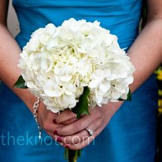 """The bridesmaids each carried an all-white bouquet made up of hydrangeas, chrysanthemums, peonies or dahlias, which stood out beautifully against the vibrant blue of their dresses."""