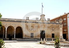 Photo taken in a square in Jerez de la Frontera in Spain. In the picture you see a particular story building with a section of the porch by the slender white columns. On the main facade there are two statues and a flagpole with a flag on the roof. In the center you see a column.