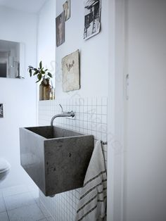 a deep wash basin made from concrete that could be in the bathroom, laundry room, or even the garage., concrete sink