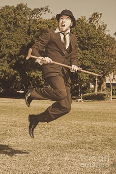 Sepia View Of A Happy Young Man With Retro Suit, Bowler Hat And Walking Stick Jumping Midair On Grass by Ryan Jorgensen