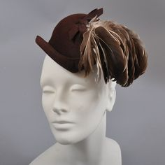 1940's hat (front view)   Brown felt cap style peaked in front and back. Trimmed with really beautiful brown and cream toned feathers in a complimentary arc to the hat